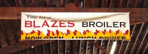 A banner from the old Blazes Broiler in Ballard now hangs in the rafters of the next-door business, Limback Lumber at 2600 NW Market Street.