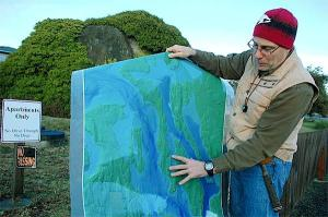 Dr. Terry Swanson of the UW stands in front of Big Rock at Coupeville, Whidbey Island. Photo courtesy of the Whidbey News-Times.