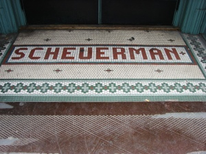 The spelling of the name of German immigrant Christian Scheurmandt was modified over time. This is the final spelling he preferred, which he had put in tiles of his building at the corner of 1st and Cherry Streets, one of the first buildings put up after Seattle's Great Fire of 1889.