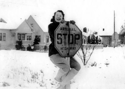 Vivacious Delores Goodwin, age 17, clowns around on the NE 89th Street stop sign in this photo taken on January 19, 1935.  The house in the background is at 8816 35th Ave NE, built in 1926.