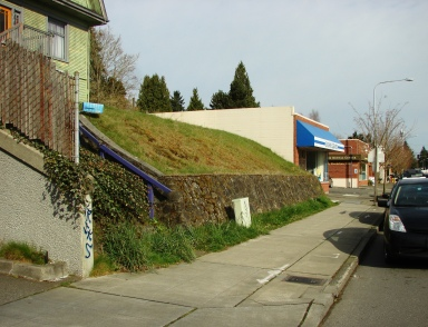 The Big Green House at 7321 35th Ave NE has a retaining wall which shows that the house was there long before road-grading.
