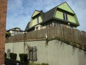 The Big Green House at 7321 35th Ave NE has a retaining wall around it, showing that the street level has been cut down.