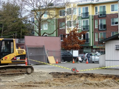 As of March 16, 2013 the hair salon building (at right) has not yet been removed. Soil is being removed from the lot due to environmental contamination from the 1950's gas station on the site. Background: Jasper Apartments at 8606 35th Ave NE.