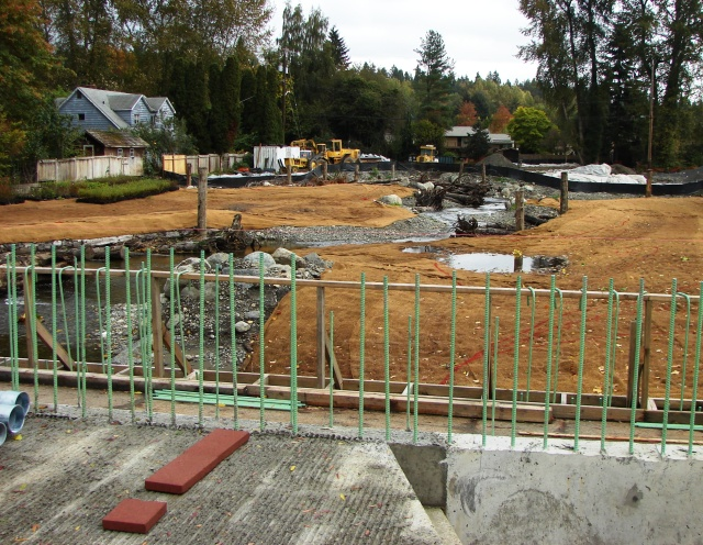 Looking eastward from 35th Ave NE, in the foreground we see the road repair work with sidewalk and rails, which will give this section a bridge-like appearance.  A flood plain is being created as the South Branch of Thorton Creek flows toward Meadowbrook Pond.  The house at left faces 36th Ave NE.