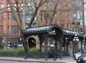 The sheltering structure of the Pioneer Square Pergola (foreground) was set up in 1909 for people waiting for the streetcar.