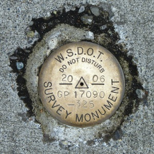 Brass survey markers are still used today, such as this 2006 marker at the Eastgate Freeway Park & Ride station in Bellevue.