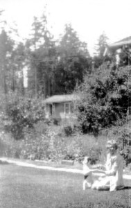 Ruth in front of the Shauer home with her dog Lindy, named in honor of the September 1927 visit of Charles Lindbergh, aviator, to Seattle. In the background is the house of the lessee who helped run the grocery store on Shauer's business block.