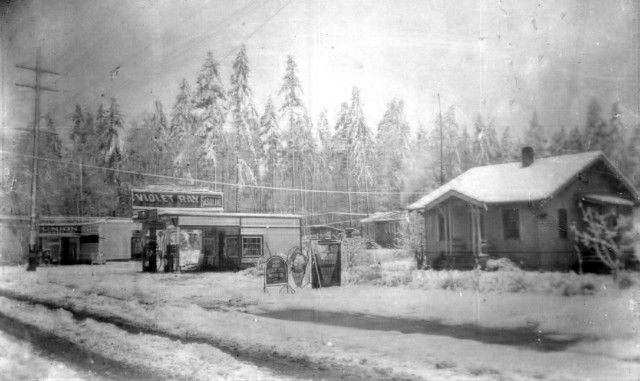 This photo circa 1927 shows the Shauers house (present site of Wells Fargo Bank) with the new gas station Mr. Shauer had opened.