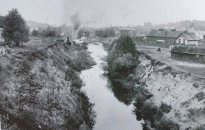 Before construction of the ship canal there was this ditch which had been created by hand-digging. Photo circa 1912, with the McMullen's Hay and Grain building at right. Photo courtesy of MOHAI 83.10.6934.
