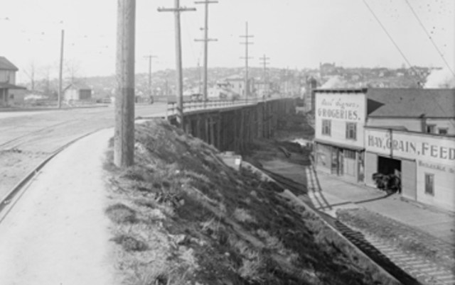 Carl Signor's grocery store is seen in this 1915 photo looking north. The posts of the trestle bridge to Fremont can be seen. On the horizon is B.F. Day School. Photo 2787, Seattle Municipal Archives.